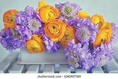 Beautiful bouquet of flowers.Yellow ranunculus flowers and scabious close-up on the table.