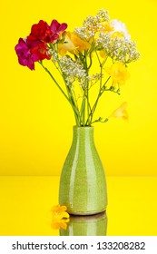 Beautiful bouquet of freesia in vase on yellow background