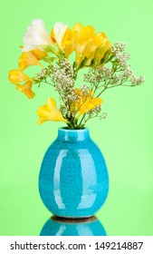 Beautiful bouquet of freesia in vase on green background