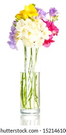 Beautiful bouquet of freesias in transparent vase, isolated on white