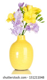 Beautiful bouquet of freesias in vase, isolated on white