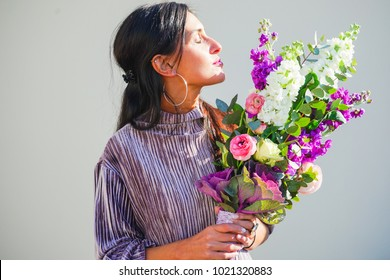 Beautiful bouquet with fresh anemone, roses, brassica, and antirrhinum flowers in a hand of beautiful smiling woman