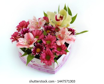 beautiful bouquet of fresh flowers: green Orchid, pink Alstroemeria, pink chrysanthemum, colorful chrysanthemum in a heart-shaped box on a white table close-up with blurred background