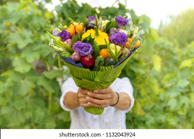 Beautiful bouquet of fresh vegetables and flowers in the hands of a woman as a gift
