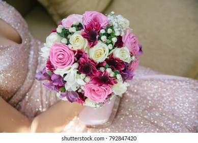 Beautiful bouquet holded by a young lady with superb shiny dress.