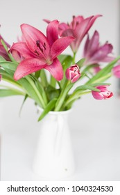 Beautiful bouquet of Lilies and Tulips over the white background. Spring light photo