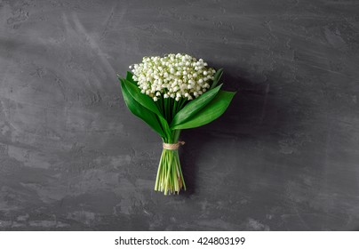 Beautiful bouquet of lilies of the valley on a dark background, top view