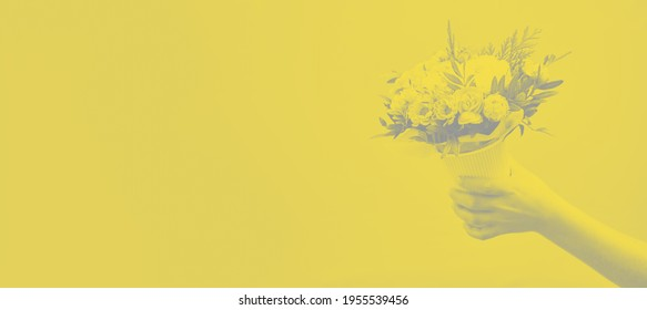 Beautiful bouquet of mixed different flowers in hand on yellow background banner with copy space, greeting, gift with color of 2021 year