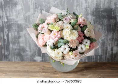beautiful bouquet of mixed flowers into a vase on wooden table. the work of the florist at a flower shop
