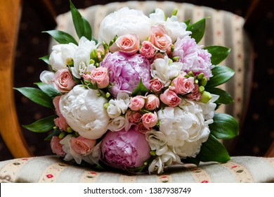 Beautiful bouquet of peonies, pink roses and freesias, against the background of the chair, top view