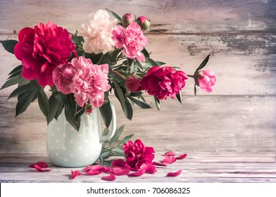 Beautiful bouquet of peonies in a vase. White, red, pink peonies against the background of a vintage wall. Country style, floral design. Toned photo.