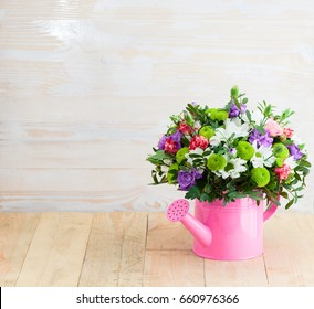 beautiful bouquet of pink, purple and white flowers in pink watering can on wooden table. Wood background