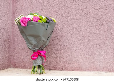 beautiful bouquet of pink roses, daisies, chrysanthemums and other flowers wrapped in gift gray paper for Mothers Day and Valentines Day