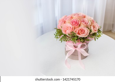 Beautiful bouquet of pink roses in a festive round box on a white table. Gift for holiday, birthday, Wedding, Mother's Day, Valentine's day, Women's Day.  Flowers in a hat box.