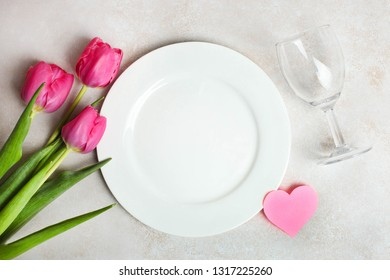 Beautiful bouquet of pink tulips, plate and wineglass on neutral background. Romantic dinner. Concept Valentine's day, International Women's Day.