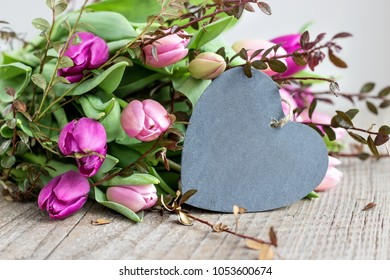 beautiful bouquet of pink and violet tulips with a heart a wooden background