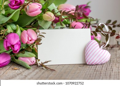 beautiful bouquet of pink and violet tulips with a heart and a white copy space