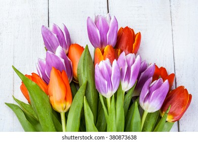 Beautiful bouquet of purple and red tulips on white wooden background