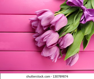 Beautiful bouquet of purple tulips on pink wooden background