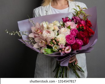 A beautiful bouquet of rare flowers with lisianthuses, ranunculus, carnations, peony roses, in the hands of a girl in white clothes with blond hair.