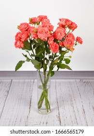 Beautiful bouquet of red roses in transparent glass vase. On white grey background