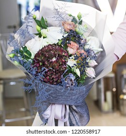 Beautiful bouquet in with roses and dark purple hydrangea. Modern, stylish bouquet in female hands