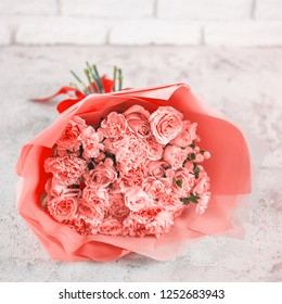 Beautiful bouquet with roses, dianthus, hypericum, clove in color of year 2019 Living Coral concept. Trendy color Living Coral in flowers, wedding bouquet. Square format
