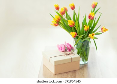 Beautiful bouquet of tulips in glass vase on table, ready to make a present on holiday with gift box for beloved person
