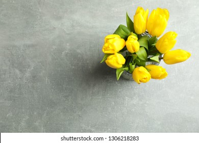 Beautiful bouquet tulips in vase on gray background, top view. Space for text