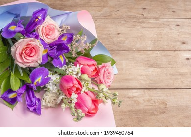 A beautiful bouquet of wedding flowers on old wooden boards. The concept for a holiday gift for Birthday, March 8 or Valentine's Day. Greeting card, a place for text