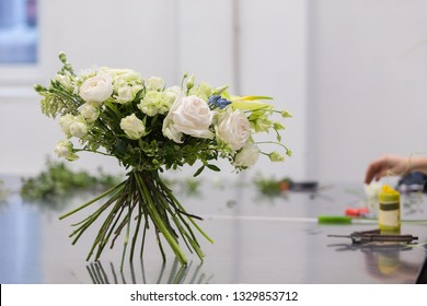 Beautiful bouquet of white flowers stands on the stems on a glossy gray table during the flower masterclass. Wedding decoration design concept