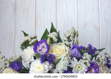 Beautiful bouquet of white and purple flowers on a white wooden background. Flower arrangement for your beloved.