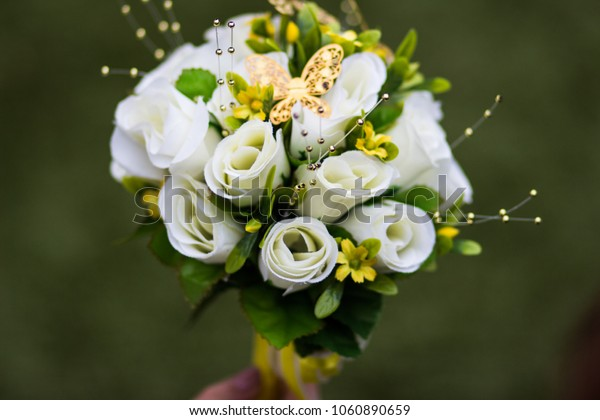A beautiful bouquet of white roses with golden butterfly on top