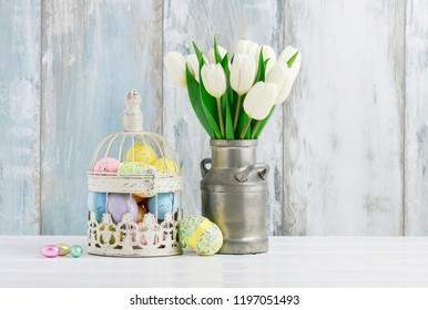Beautiful bouquet of white tulips and vintage bird cage full of colorful Easter eggs.