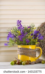 Beautiful bouquet of wildflowers in cup and berries on wooden table