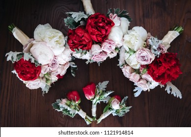 Beautiful bouquets from fresh flowers of peonies and roses of red and pink color lie on a table. Four bouquets of bridesmaids and a buttonhole of friends of the groom lie on a table.