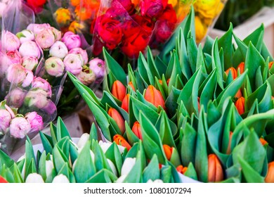 Beautiful bouquets of various tulips are presented in street flower shop