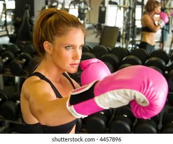 Beautiful boxing girl wearing pink gloves.