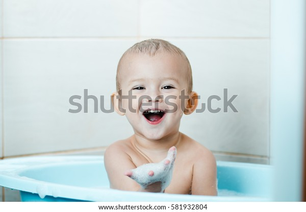 Beautiful boy bathing a toddler in the tub clean and hygienic,looks at the hand which in the foam