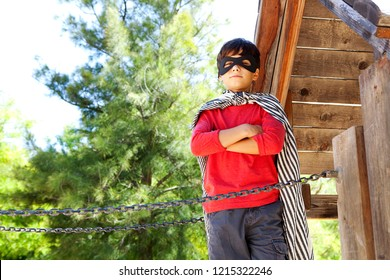 Beautiful boy child standing on wooden structure treehouse in park playground dressed as superhero, powerful in sunny outdoors. Kid role playing imagination, leisure recreation fun lifestyle.