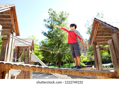 Beautiful boy child standing on wooden structure bridge in park playground dressed as superhero pretending to fly, sunny outdoors. Kid role playing imagination, leisure recreation fun lifestyle.