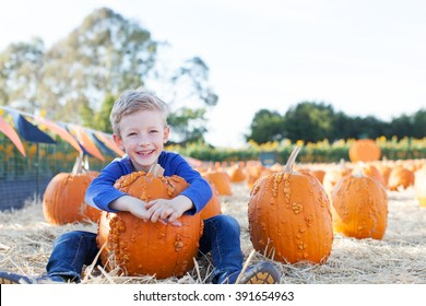beautiful boy enjoying autumn time at pumpkin patch holding huge pumpkin