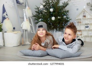 beautiful boy and girl, brother and sister, having fun in xmas decorated room