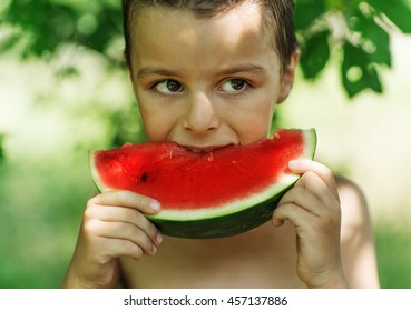 beautiful boy holding a piece of watermelon and eat