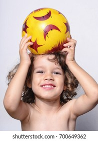 Beautiful boy playing with a ball. Cute toddler holding in his hands a football ball, looking interested in this sport