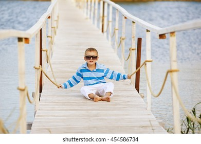 beautiful boy posing sitting on a wooden bridge . Dressed in a nautical theme .