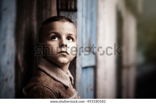 beautiful boy with short hair looking up against the wall of the old house