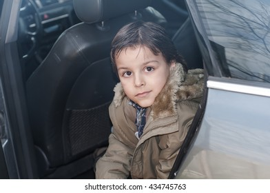 beautiful boy sitting in the back seat of the car
