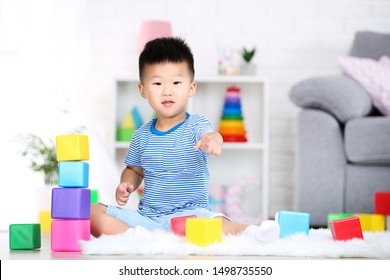 Beautiful boy sitting and playing with plastic toys at home