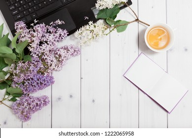 Beautiful branch of white and violet lilac flowers with opened note-book and black opened laptop, lying on the white wooden background with cup of tea, mock up flat top view